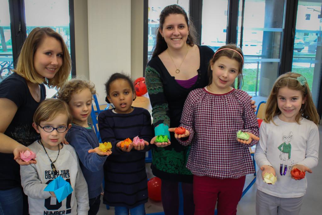 Codeuses et enfants Lopica avec des origamis